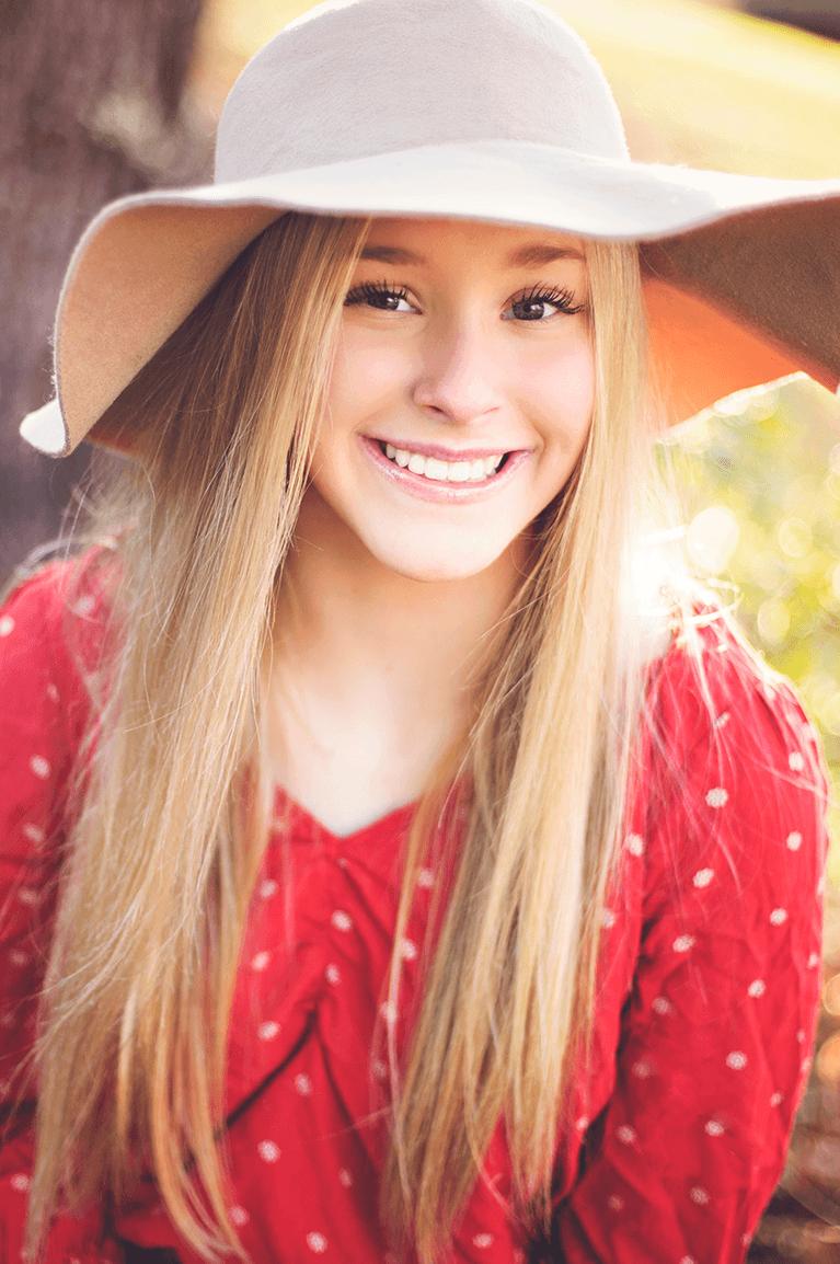 Teen girl Invisalign patient wearing hat
